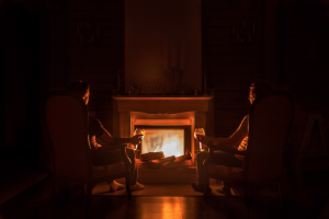 "alt=""two people sitting in front of a fireplace"""