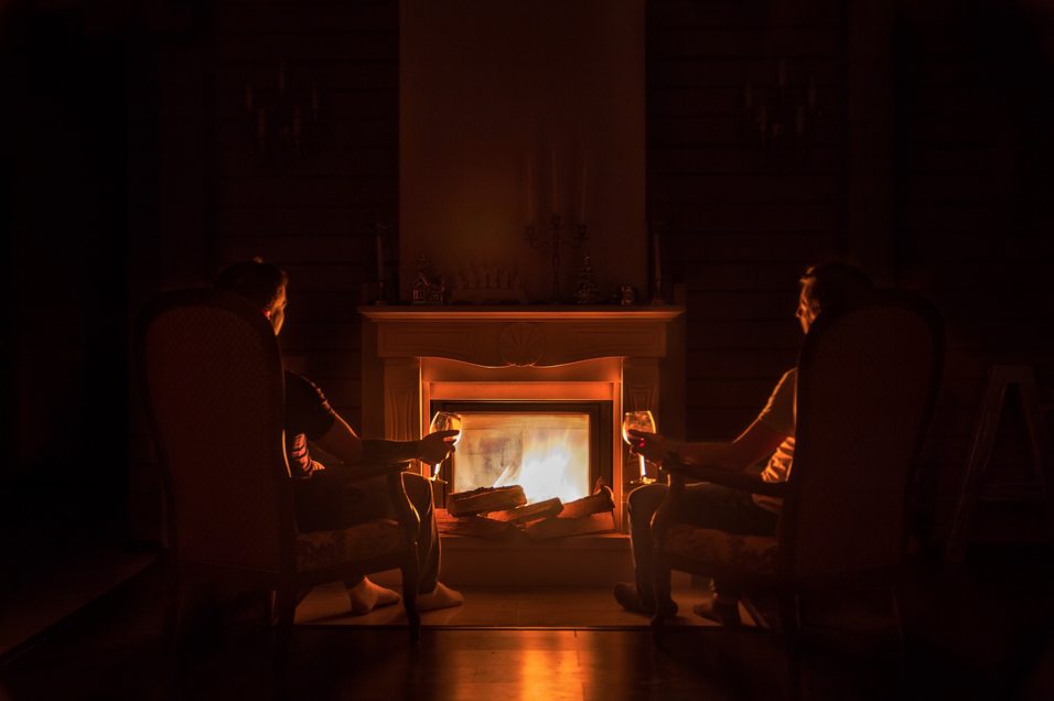 """alt=""""two people sitting in front of a fireplace"""""""